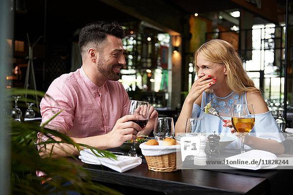 Junge Frau mit lachendem Freund am Restauranttisch