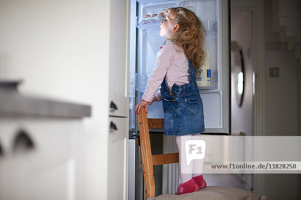 Young girl standing on chair  looking into fridge