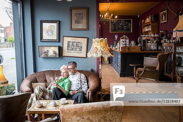 Schrulliges Vintage-Paar betrachtet Smartphone in Teestuben