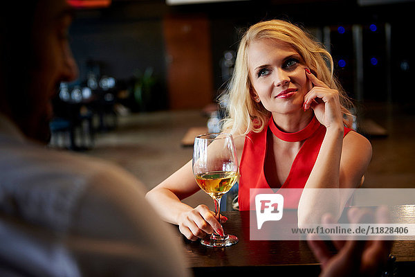 Young woman flirting with barman sitting at bar