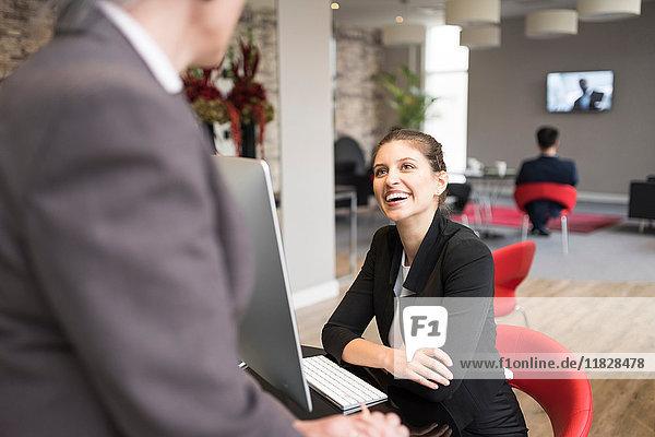 Junge Geschäftsfrau und Kollegin sprechen über Bürotisch