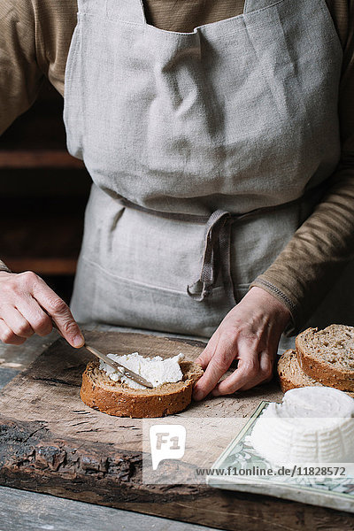 Woman spreading ricotta cheese onto slice of bread  mid section