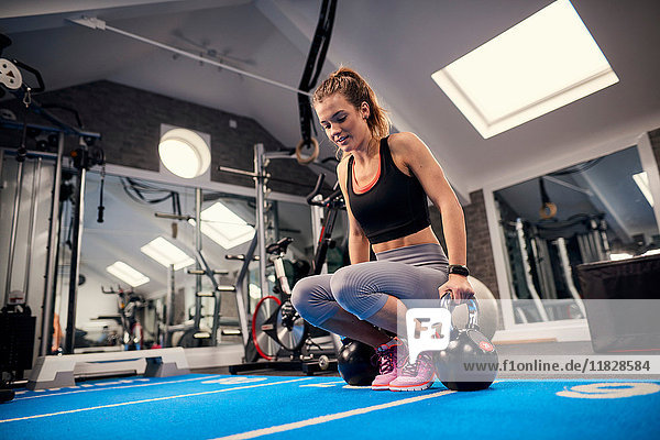Young woman training  preparing to lift kettle bells in gym