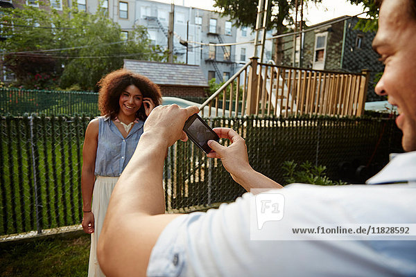 Young man photographing woman in garden