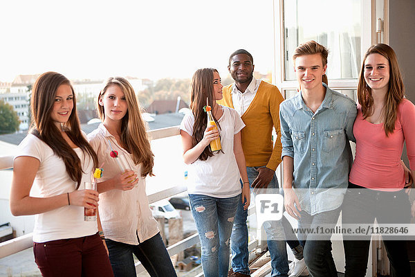 Group of friends at house party on balcony