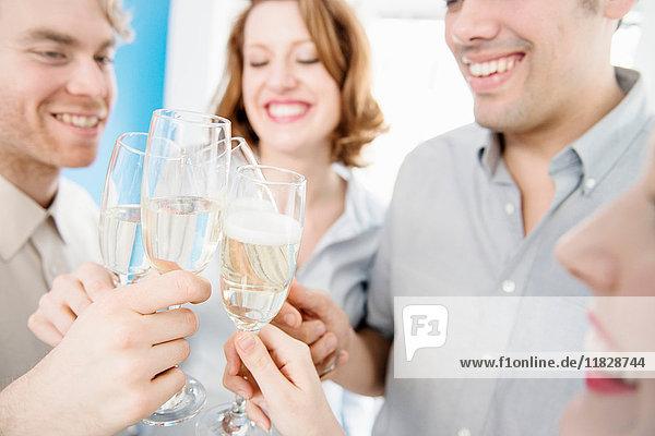 Kollegen stoßen mit Champagnergläsern an