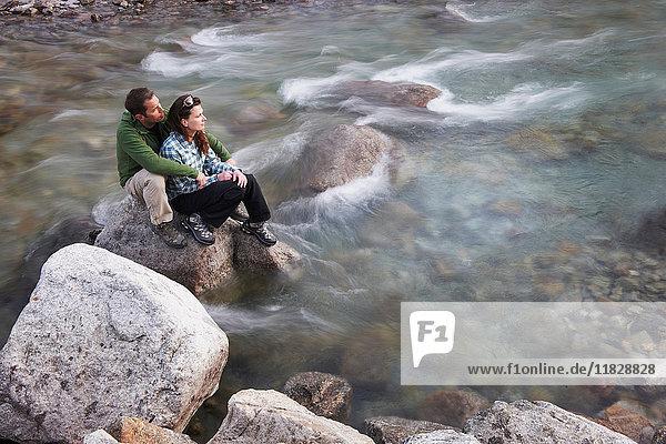 Mittelgroßes erwachsenes Paar sitzt auf Felsen im Fluss