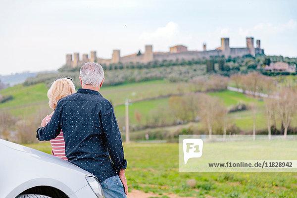 Rückansicht eines Touristenpaares mit Blick auf eine Festung in der Landschaft  Siena  Toskana  Italien