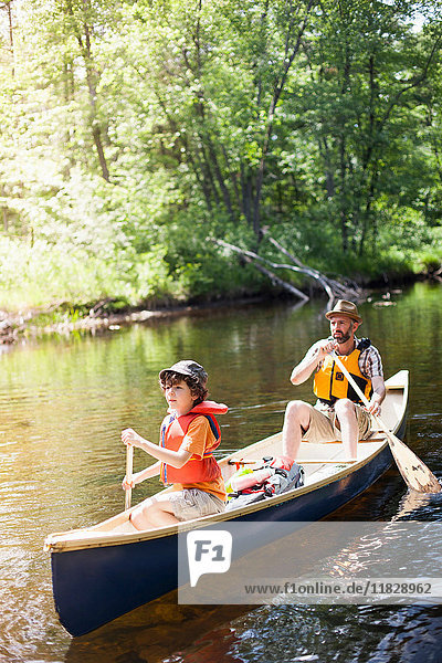 Father and son paddling canoe on river