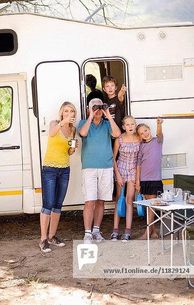 Familie benutzt Fernglas auf dem Campingplatz