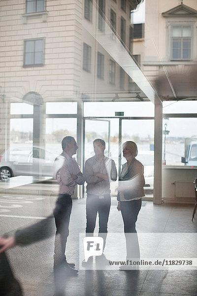 Geschäftsleute im Fenster gespiegelt