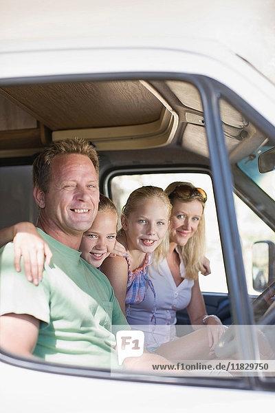 Gemeinsam lächelnde Familie im Wohnmobil