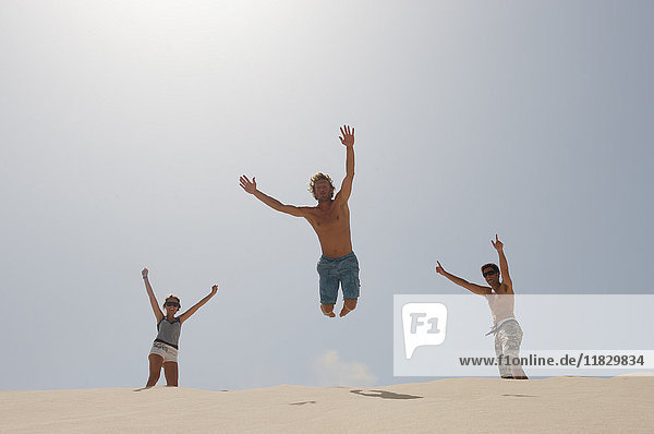 Man jumping over a big sand dune