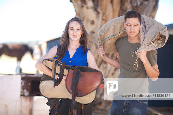Young couple carrying saddle and sack of hay