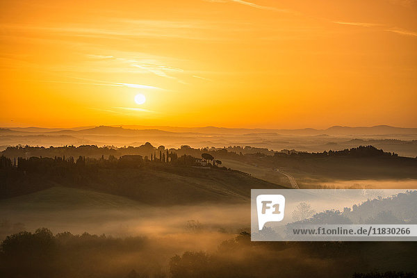 Sunrise over foggy rural landscape