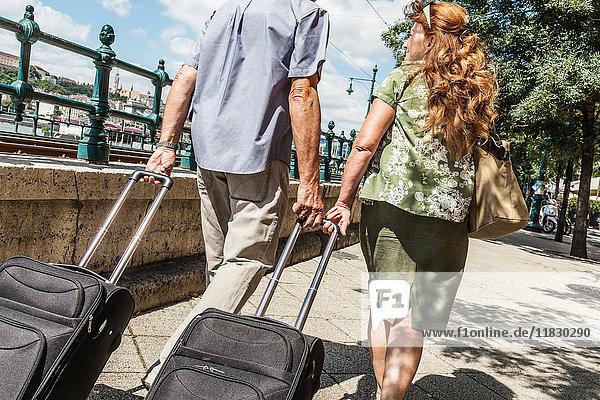 Älteres Paar rollt Gepäck auf der Straße