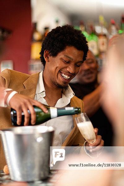 Barkeeper schenkt Champagner an der Bar ein