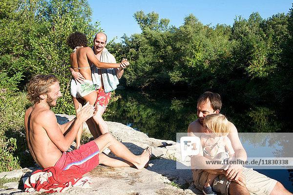 Familie entspannt in Badeanzügen am Fluss