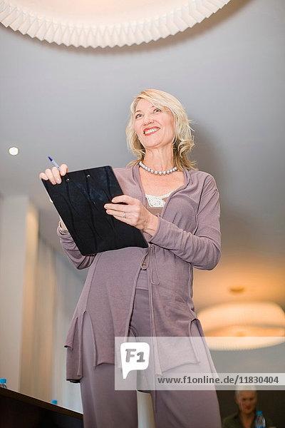 Geschäftsfrau mit Zwischenablage im Büro