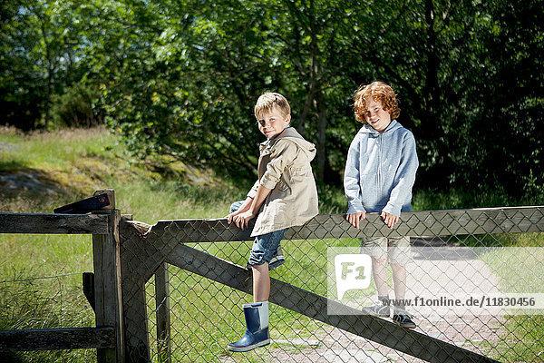 Children climbing wooden fence outdoors