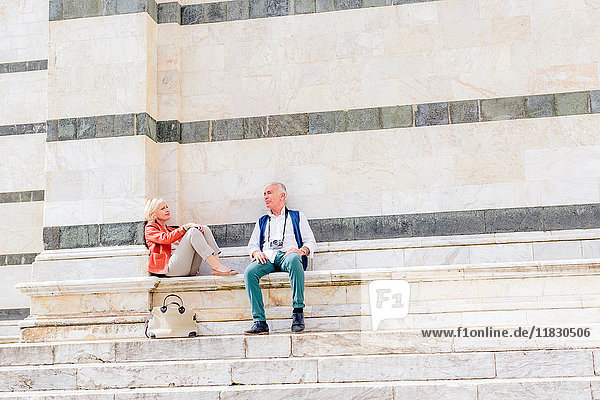 Tourist couple sitting on Siena cathedral stairway  Tuscany  Italy