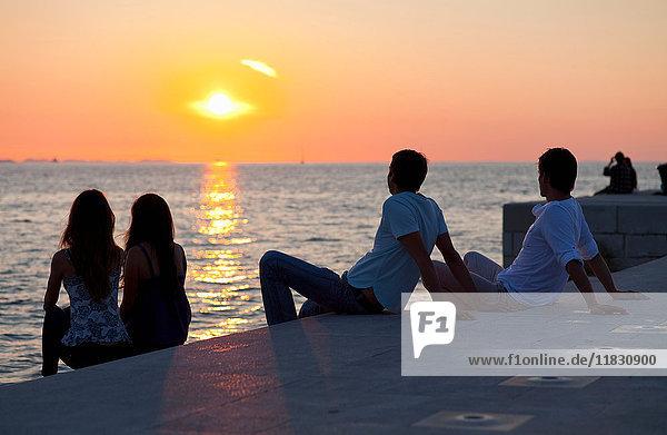 Paare entspannen sich auf dem Pier im Freien