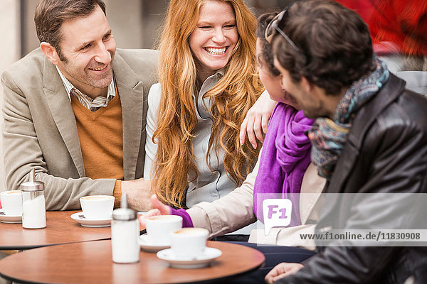 Paare trinken Kaffee im Straßencafé