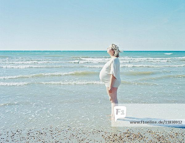 Schwangere Frau am Strand stehend
