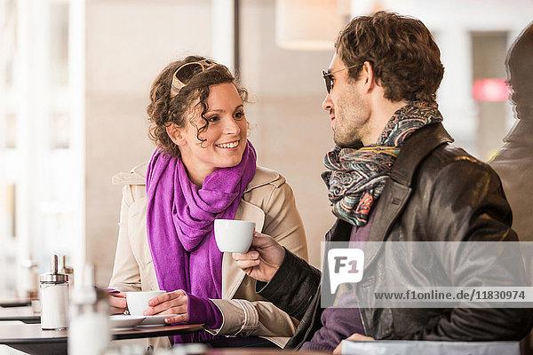 Ehepaar trinkt Kaffee im Straßencafé