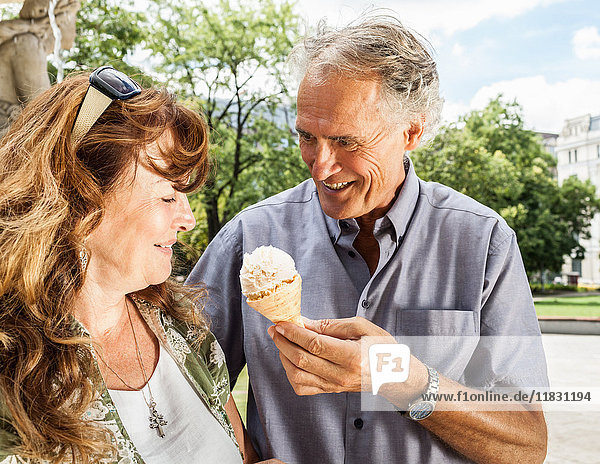 Older man offering wife ice cream