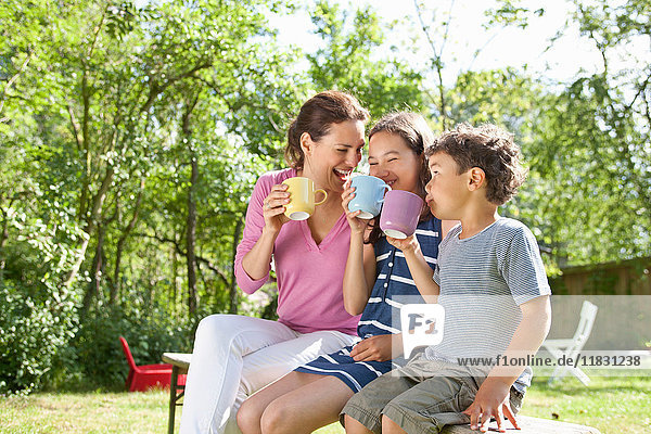Mother and children drinking outdoors