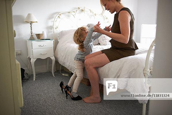 Mutter hält Tochter  die in hochhackigen Schuhen balanciert