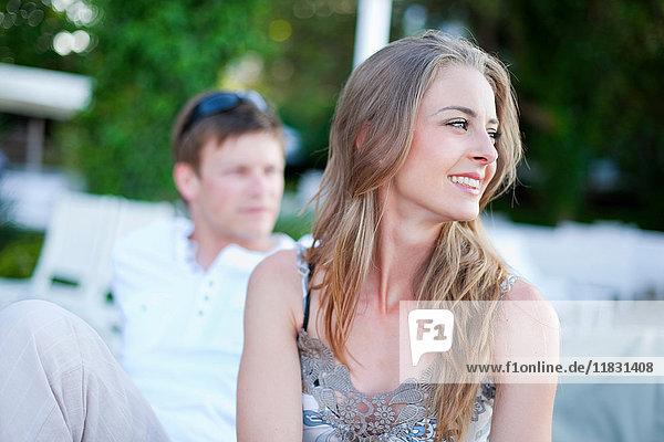 Lächelnde Frau sitzt im Freien