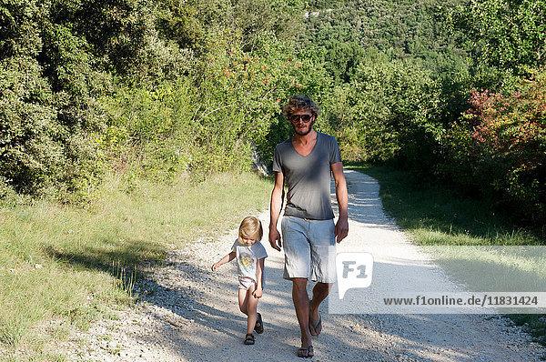Vater und Tochter gehen auf dem Feldweg
