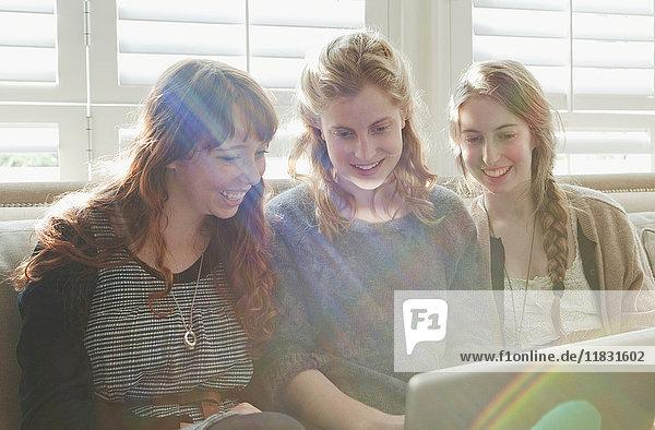 Mädchen im Teenageralter mit Laptop auf der Couch