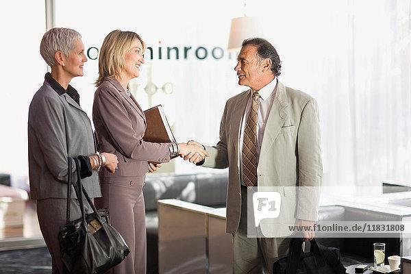 Geschäftsleute schütteln sich im Büro die Hand