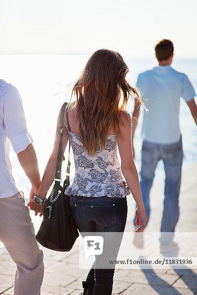 Paare gehen Hand in Hand im Freien