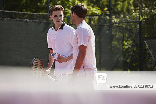 Tennisspieler mit Tennisschlägern im Gespräch auf dem sonnigen Tennisplatz