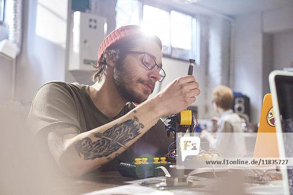 Fokussierter Jungdesigner bei der Montage von Robotern in der Werkstatt