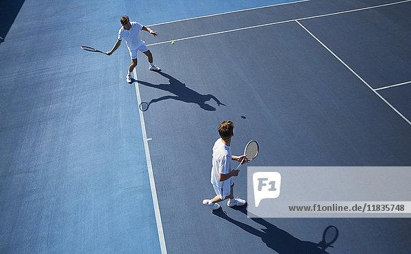 Junge Männer verdoppeln Tennisspieler beim Tennisspielen auf dem sonnigen blauen Tennisplatz