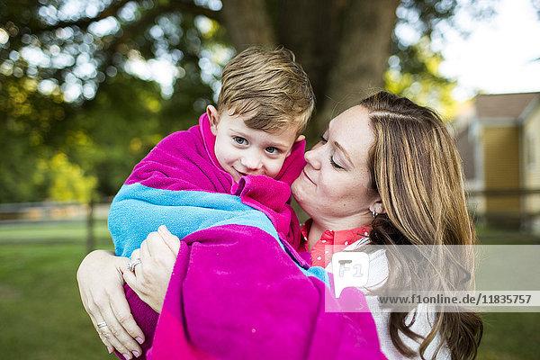 Liebevolle Mutter hält den Sohn in ein Handtuch gewickelt im Sommerhof.