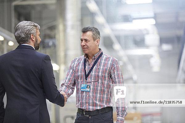 Geschäftsmann und Vorgesetzter beim Händeschütteln in der Fabrik