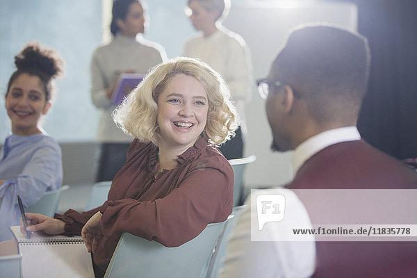 Lächelnde Geschäftsfrau  die sich umdreht und dem Geschäftsmann im Konferenzpublikum zuhört.