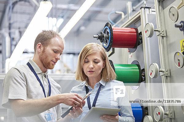 Arbeiterinnen und Arbeiter mit digitalem Tablett in der Faseroptikfabrik