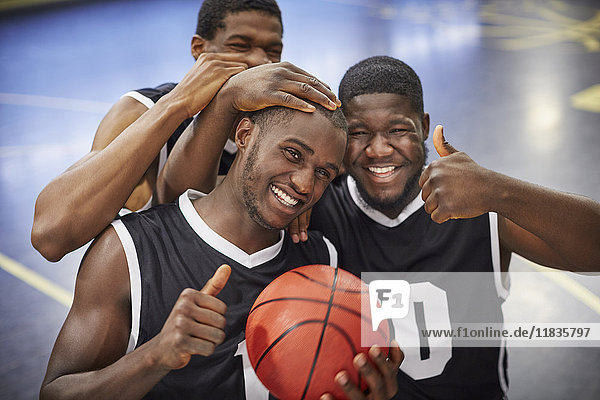 Portrait lächelndes, selbstbewusstes, junges Basketballteam feiert, Daumen hoch gestikulierend