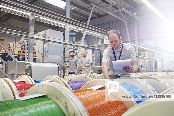 Arbeiter mit Zwischenablage zur Überprüfung von Mehrfarbenspulen in der Glasfaserfabrik