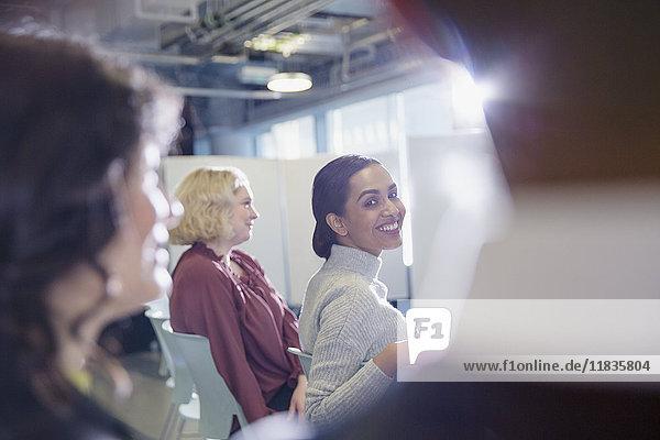 Lächelnde Geschäftsfrau blickt zurück ins Konferenzpublikum