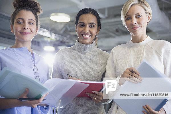 Portrait lächelnde  selbstbewusste Geschäftsfrau mit Papierkram