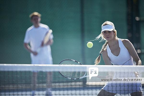 Entschlossene junge Tennisspielerin, die auf einem sonnigen Tennisplatz den Ball am Tennisnetz schlägt.