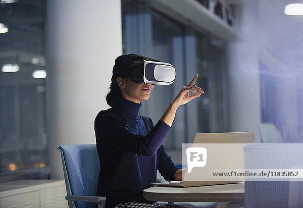 Geschäftsfrau mit Virtual-Reality-Simulator am Laptop im Büro